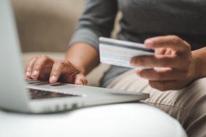 Internet shopper entering credit card information using laptop keyboard
